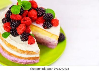 Sponge cake with vanilla cream and fresh berries on white table.