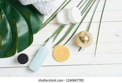 Sponge on the table, face mask and leaf of a plant