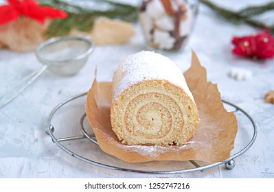 Sponge roll with curd cream in the New Year and Christmas decoration on a gray background.