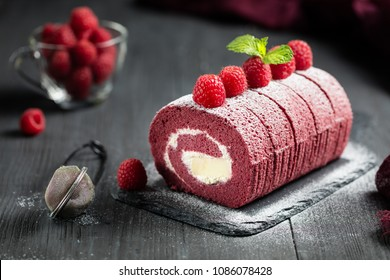 Sponge Swiss roll with fresh raspberry and sugar icing on dark background