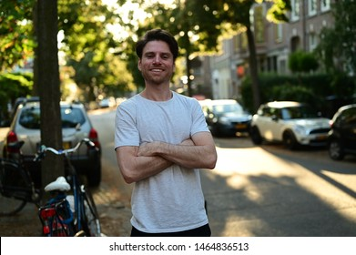 Spontaneous male master student smiling and standing with his arms crossed in a traditional street in Amsterdam, the Netherlands