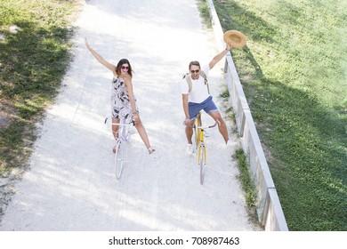 A spontaneous romantic tourist couple riding a bike on a cycle lane. Fashion blonde boyfriend and girlfriend walking on the park with vintage bike.. concept love