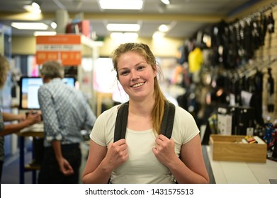 Spontaneous and smiling backpacker girl standing in a local camera store with many photography related accessoires