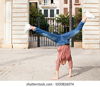 Spontaneous young woman sightseeing on city holiday, doing cartwheel at stone monument, expression of joy, outdoors. Teenager celebrating dynamic energy fun, travel recreation leisure lifestyle.