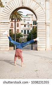 Spontaneous young woman sightseeing on city holiday, doing cartwheel under stone architecture arch monument, outdoors. Teenager celebrating dynamic energy fun, travel recreation leisure lifestyle.