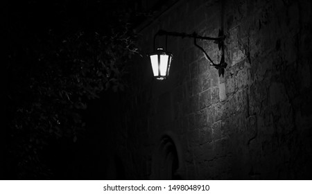 Spooky black and white alley with a lit street lamp