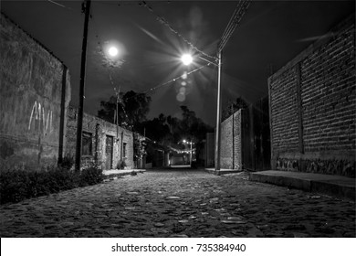 Spooky black & white night shot in empty mexican rural town with full moon