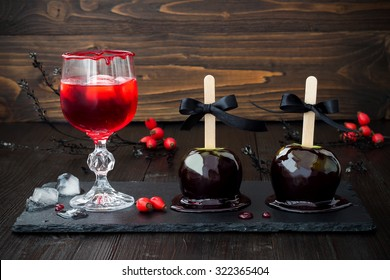 Spooky bloody cocktail and black poison caramel apples. Traditional dessert and drink recipe for Halloween party. Selective focus