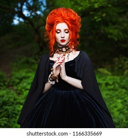 Spooky carnival attire. Sorceress woman with pale skin and red hair in black mystical gown and renaissance bracelet on hand pronounces witchcraft. Spooky outfit for carnival. Sorceress witchcraft