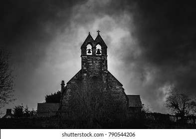 Spooky Church bells at night with moonlight behind. St Thomas Church, Halford, Craven Arms, Shropshire, England, UK.
