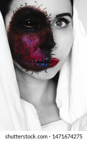Spooky close-up portrait of a woman with black eye and a cursed mark on her face on white background. Demonic spirit in an innocent body concept