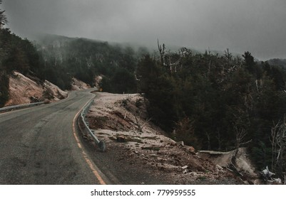 Spooky, dangerous road through the Andes mountains on the Patagonia border between Chile and Argentina with a steep drop into forests on one side and the mist of low clouds up ahead