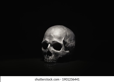 Spooky dark black skull aginast dark background closeup