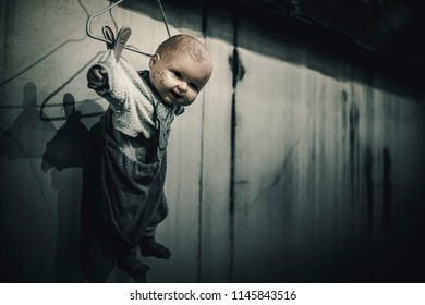 Spooky doll hang on the wall in haunted house. Halloween scary doll concept.