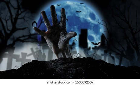 Spooky graveyard with zombie hand coming out of the ground.