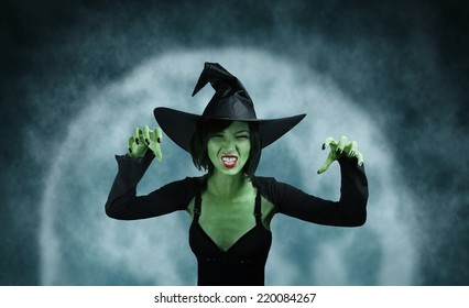 Spooky green witch performs magic on full moon background. Halloween, horror theme