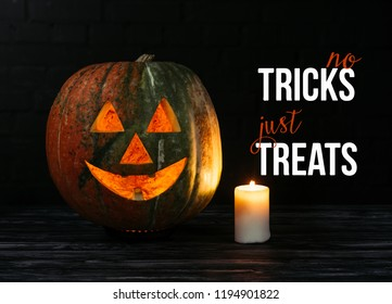 "spooky halloween carved pumpkin with candle on wooden table on black background with ""no tricks just treats"" halloween lettering"