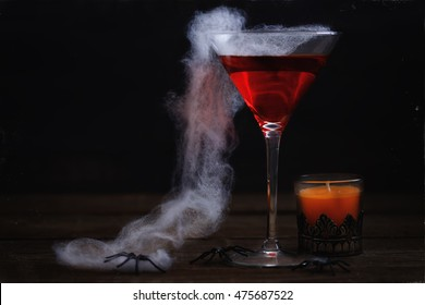Spooky Halloween drink, spider web and orange candle over rustic wooden background. Aging effect, colour toning, atmospheric noise and scratches