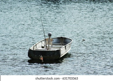 Spooky Halloween skeleton in fishing boat on lake at dusk with skeleton of a fish on his fishing pole