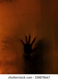 Spooky hand behind a glass in an abandoned house
