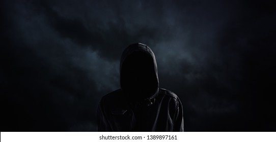 Spooky hooded person with obscured face against the dark dramatic sky