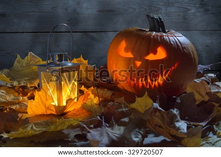 Spooky jack o lantern among dried leaves on wooden fence background