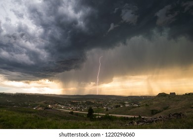 Spooky mothership supercell thunderstorm over town in USA on spring afternoon with lightning striking the ground
