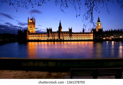 Spooky Night view of Palace of Westminster over dramatic blue sky, seen from South Bank.