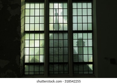 Spooky old church windows with shadows and sylhouettes.