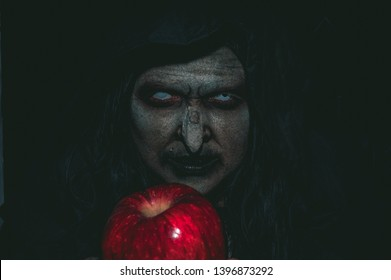 Spooky Old Witch Holding Red Apple
