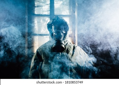 Spooky person in gas mask and an abandoned building with eerie feeling.