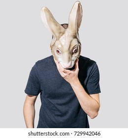 Spooky portrait of man wearing mask of rabbit standing against plain background