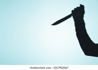 spooky shadow of person holding knife in hand on blue