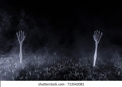 Spooky Skeleton Arms / Pair of white skeleton arms protruding from the ground, reaching upward through a fog and into a dark night sky.