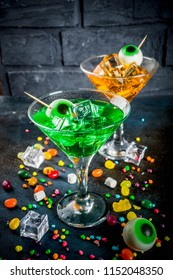 Spooky treats for Halloween, a bright green, orange martini cocktail with ice cubes and a decor of marshmallow eyes. On a dark blue background, space for text