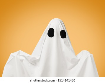 Spooky white ghost with black eyes on yellow background. Halloween costume.