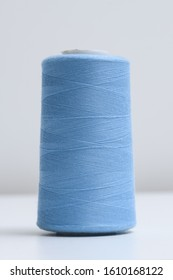 Spool of blue synthetic or cotton threads on white background. Spool of yarn using for weaving in textile manufacturing