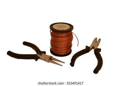 Spool of copper wire and tools on a white background