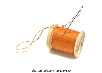 spool of orange thread on white background