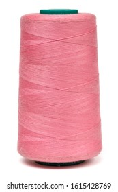 Spool of pink synthetic or cotton threads isolated on white background. Spool of yarn using for weaving in textile manufacturing