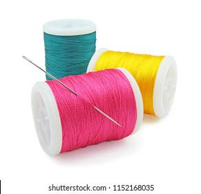 Spool of pink yellow and green thread with needle, Bobbins thread, Material of sewing tool, Isolated on white background, Cut out with clipping path