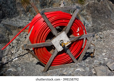 Spool of  red cable and fiber optics in the road background. Building of road in Norway