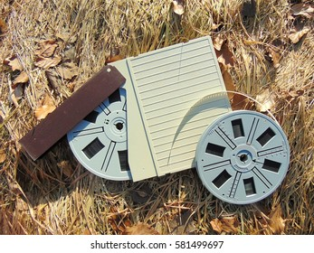 Spool of Super 8 film with cover laying in straw