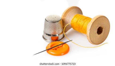 spool of thread and buttons on white isolated background