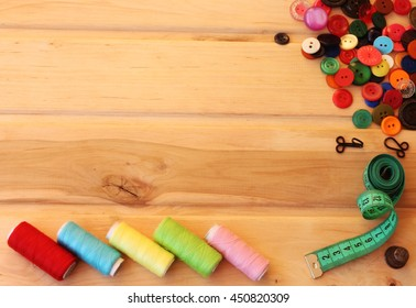 Spool of thread, colorful buttons, measuring tape on wooden background. Sewing accessories.