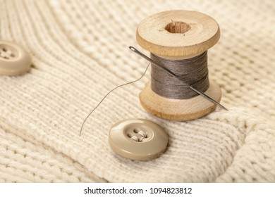 spool of thread with a needle on white knitted clothes