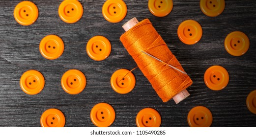 spool of threads and buttons on a wooden background