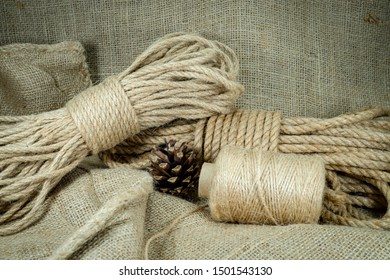 Spools of burlap threads or jute twine, sackcloth fabric in close-up on rustic grey background