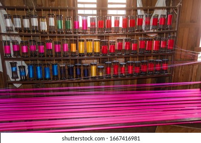 Spools of multicolored threads for making silk products and pink silk warp thread of a hand loom, Myanmar, Inle Lake,