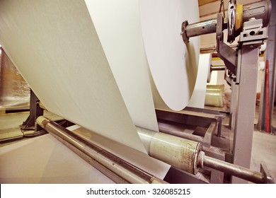 Spools of paper .Working print machine. selective focus on metal shafts and screws